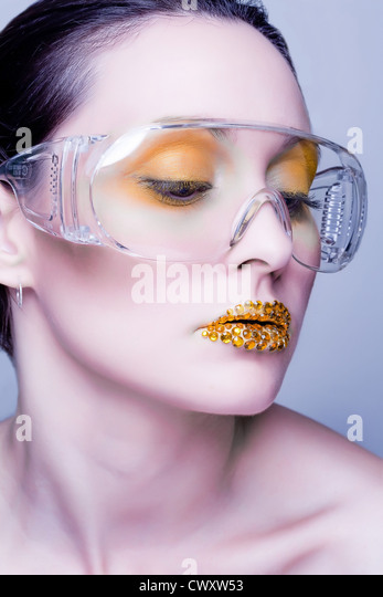 Young caucasian woman with gold fashion makeup wearing clear glasses and gold diamonties on her lips - Stock-Bilder