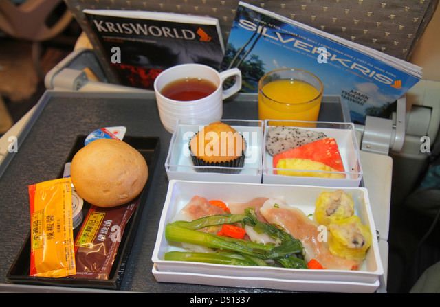 Hong Kong China International Airport HKG Singapore Airlines onboard meal tray breakfast dumplings fruit bread roll - Stock Image