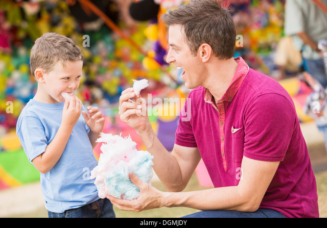 USA, Utah, Salt Lake City, Happy father with son (4-5) in amusement park eating cotton candy - Stock Image