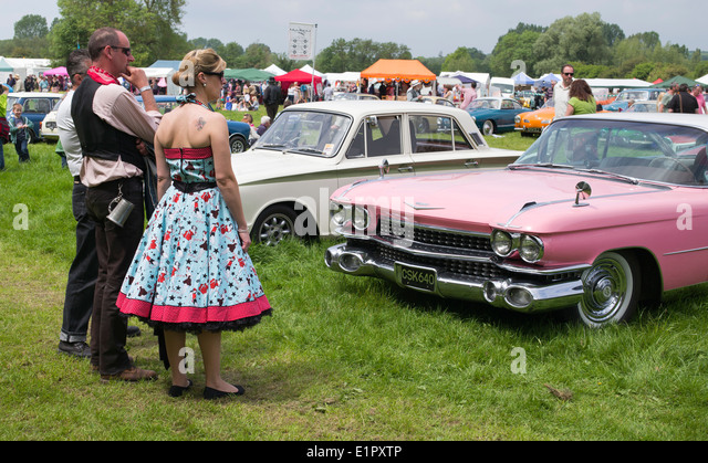 People dressed up at a Nostalgic and vintage show looking at a pink Cadillac. England - Stock Image