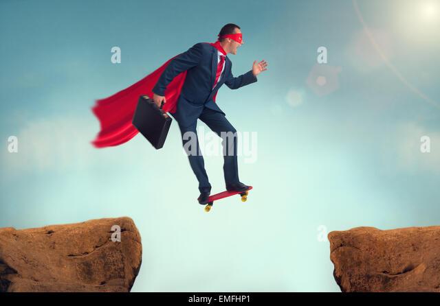 superhero businessman challenge making a risky leap of faith on a skateboard - Stock Image