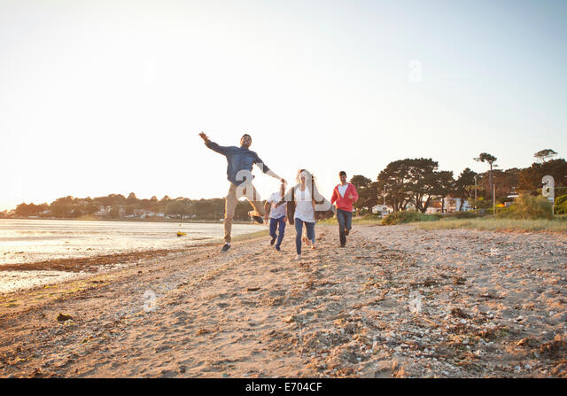 Group of friends having fun on beach - Stock Image