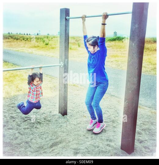 A mother and child each find adjoining pull-up bars just their size for exercise and playtime fun outdoors near - Stock-Bilder
