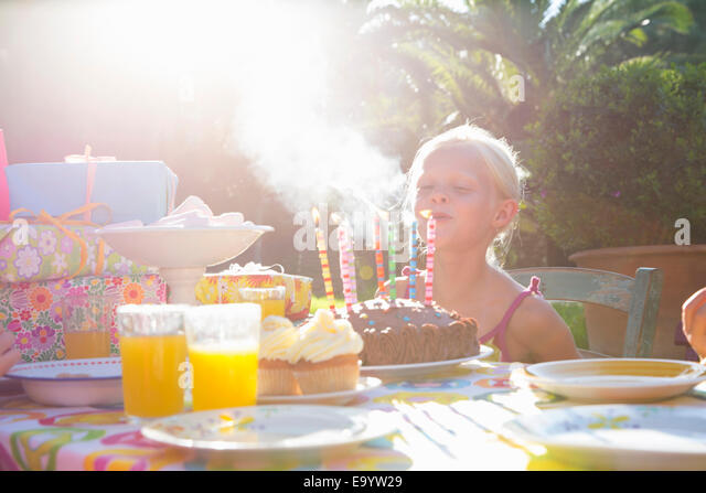 Girls blowing out candles on birthday cake - Stock Image