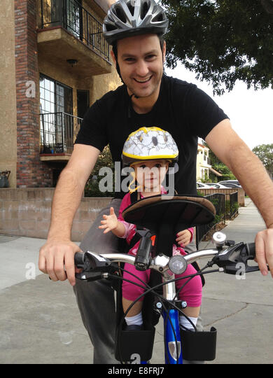 Father and daughter (18-23 months) cycling together - Stock Image