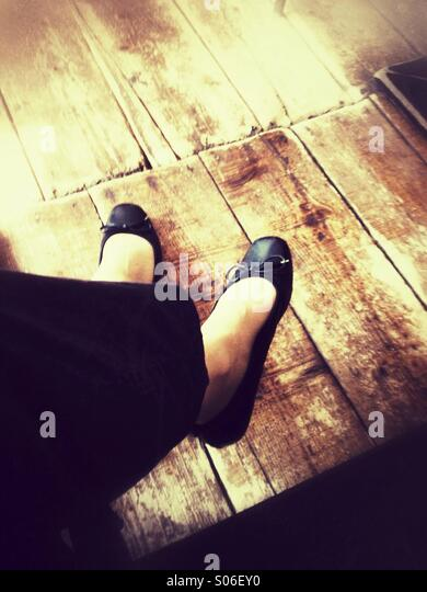 Woman's feet under the table above an Old wooden floor. Retro styled postprocessing. - Stock-Bilder