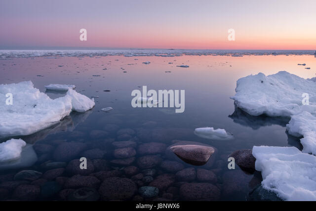 Scenic seascape with sunset and nice stones under the water at winter time - Stock Image
