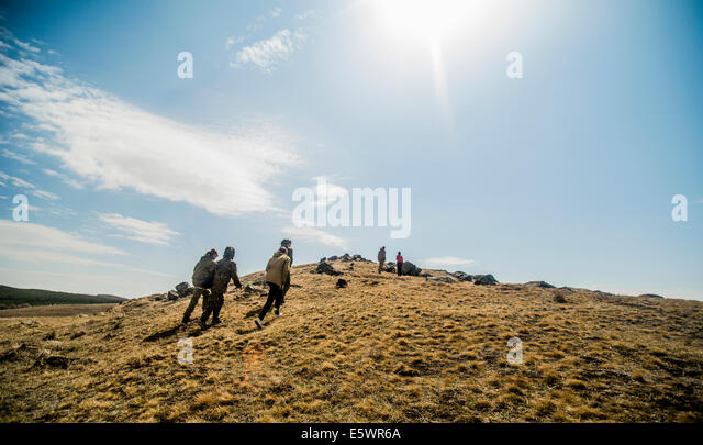 Group of six young adults hiking on mountain - Stock Image