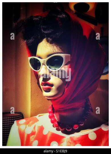 A mannequin wearing a head scarf, sunglasses and a red polka dot dress - Stock Image