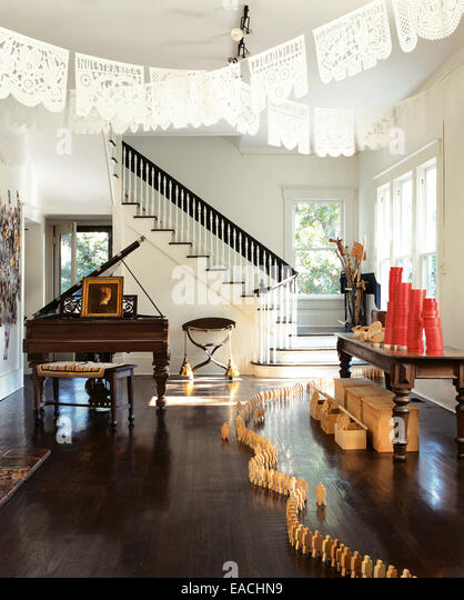 living room with formal piano and wooden figure decorations - Stock Image