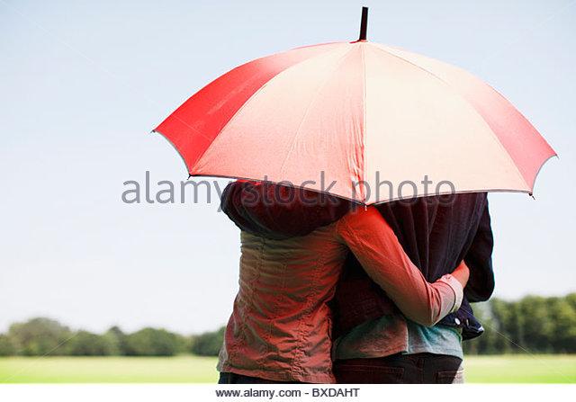 Couple hugging underneath red umbrella - Stock-Bilder