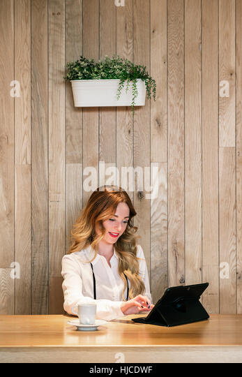 Elegant an pretty businesswoman working with a tablet in a restaurant - Stock Image