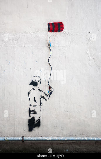 Dynamite graffiti using a hanging electrical wire on a wall in Hong Kong - Stock Image
