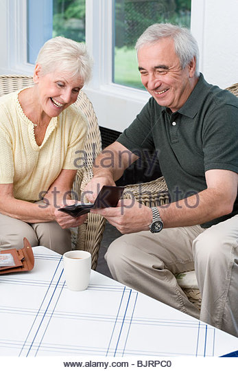 Senior man and woman looking at pictures - Stock Image