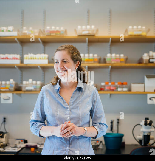 Mid-adult woman in laboratory with hands clasped - Stock Image