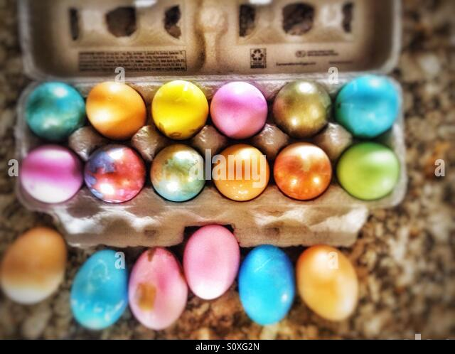 One and one half dozen colored eggs in a cardboard carton. - Stock Image