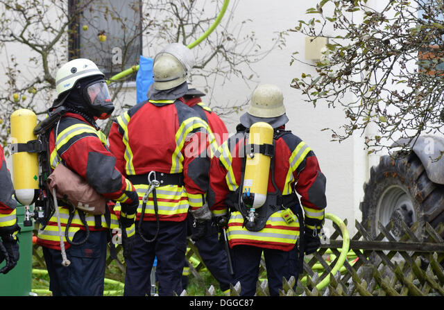 Firefighters wearing breathing equipment while extinguishing a roof fire, Aichwald, Baden-Wurttemberg - Stock Image