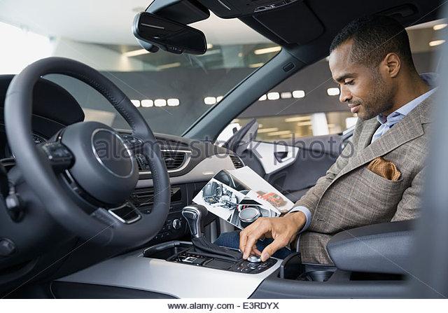 Man looking inside car in car dealership showroom - Stock Image