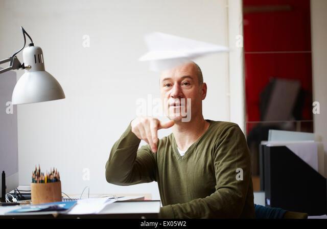 Mature man at desk throwing paper airplane - Stock Image