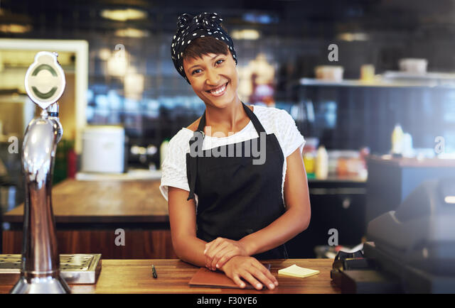 Warm welcoming young business entrepreneur standing behind the counter in her cafe giving the camera a beaming smile - Stock-Bilder