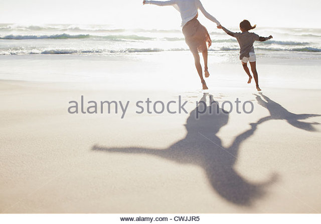 Mother and daughter holding hands and running on sunny beach - Stock-Bilder