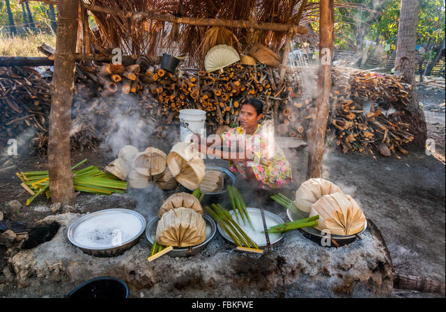 Woman boils sap from extracted palmyra palm tree in Rote Island as a part of the sugar making process. © Reynold - Stock Image