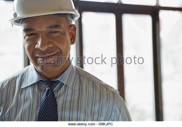 Portrait of male architect wearing hardhat at construction site - Stock-Bilder