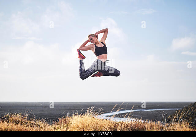 Young women leaping by a deserted unmade road in Southern Iceland - Stock Image