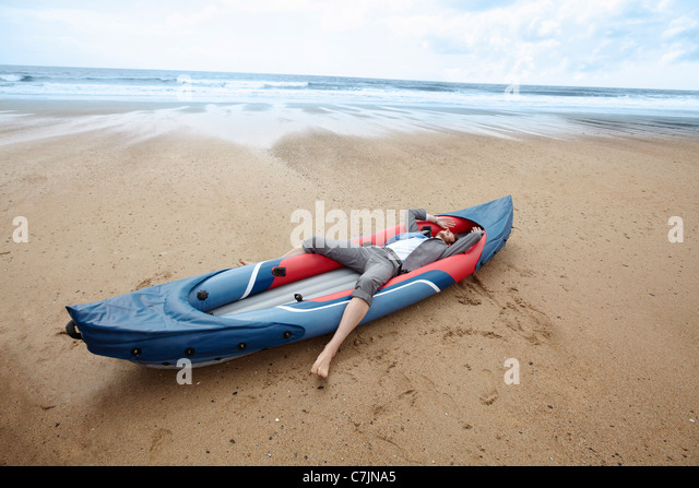 Businessmen laying in canoe on beach - Stock Image