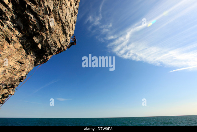 A climber scales cliffs near Swanage, Dorset, England, United Kingdom - Stock Image
