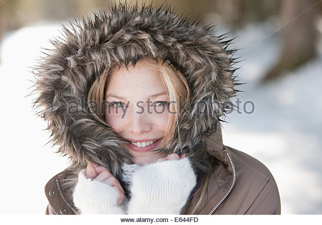 Portrait of smiling woman wearing fur hood coat - Stock Image