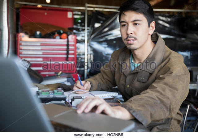 Focused male design professional engineer working at laptop in workshop - Stock Image