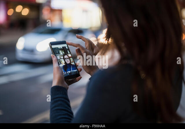 Woman taking a selfie by the roadside - Stock Image