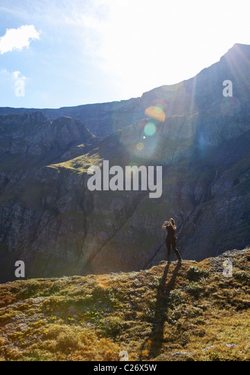 Woman Standing on the Edge of a Mountain Taking a Photograph - Stock Image