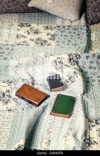 three old books on a vintage bed - Stock Image