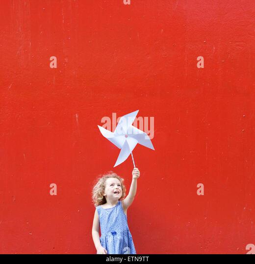 Smiling girl holding a pinwheel in the air making a Hong Kong flag - Stock Image