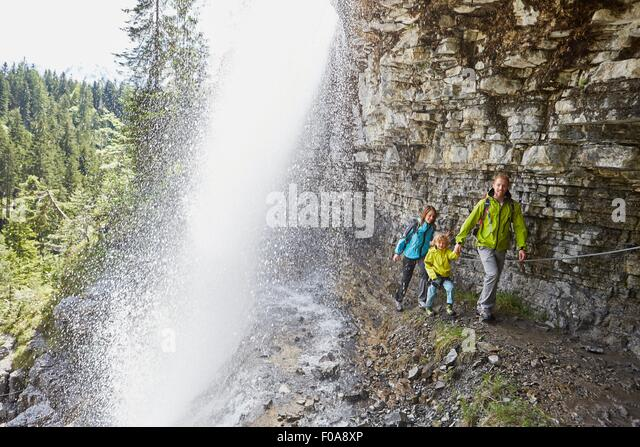 Young family, walking underneath waterfall - Stock-Bilder