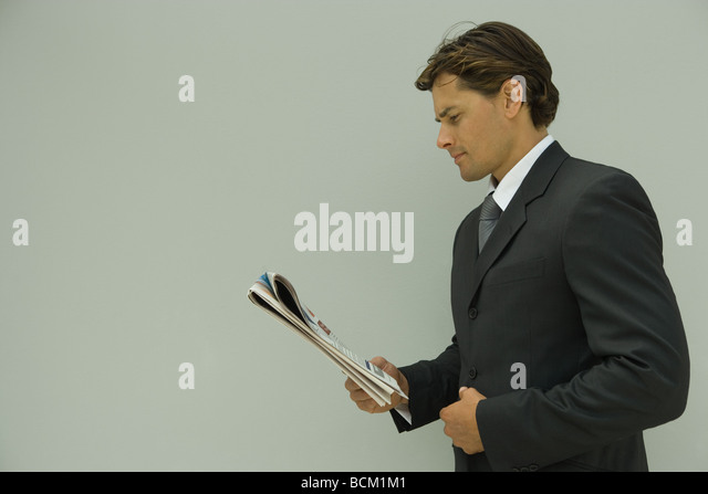 Businessman reading newspaper, side view - Stock Image