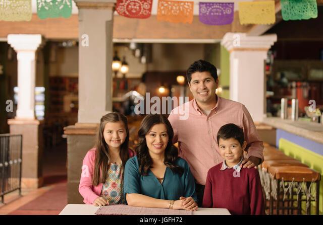 Portrait of smiling Hispanic family in restaurant - Stock Image