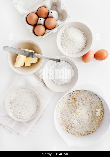 Bowls of sugar, flour, eggs, butter - Stock Image