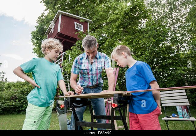 Man boys constructing building garden wood - Stock Image