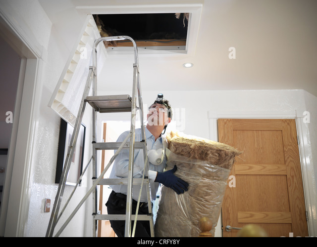 Worker carrying insulation to attic - Stock-Bilder