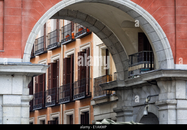Balconies and Windows with Shutters Viewed through an Arch of a Building, Plaza Mayor, Madrid, Spain - Stock Image