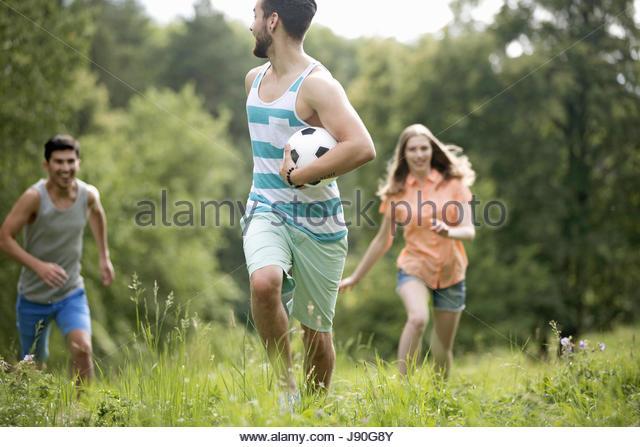 Couples Running Through Summer Field With Soccer Ball - Stock-Bilder