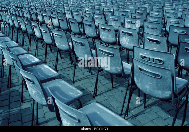 Rows of grey plastic chairs - Stock Image