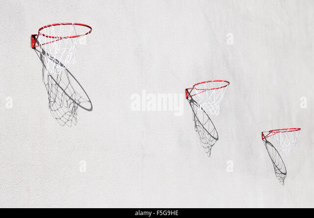 Three netball hoops with shadows on a wall - Stock Image
