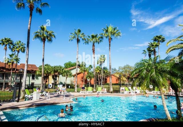 Kissimmee Florida Legacy Vacation Club Kissimmee resort hotel timeshare program lake swimming pool palm trees families - Stock Image