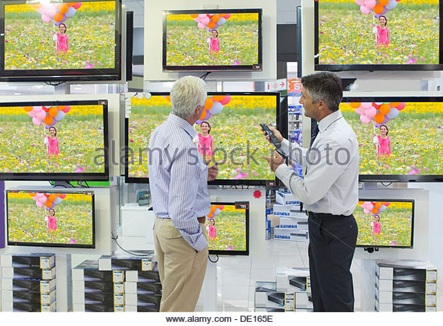 Salesman showing senior man flat screen televisions in electronics store - Stock Image
