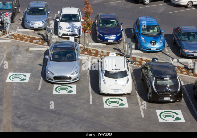 Different types of plug-in electric cars parked at EV charging stations in a company parking lot - Stock Image