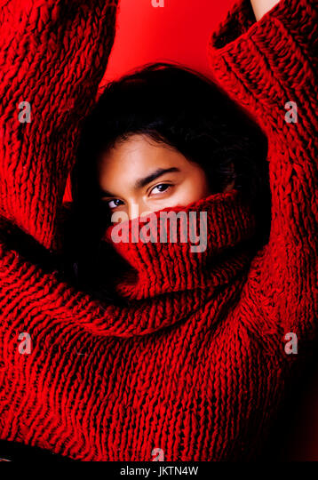 young pretty indian mulatto girl in red sweater posing emotional, fashion hipster teenage, lifestyle people concept - Stock Image